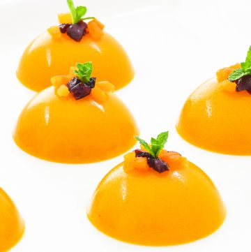 round mango puddings with mint and dry fruit toppings placed on a white plate.