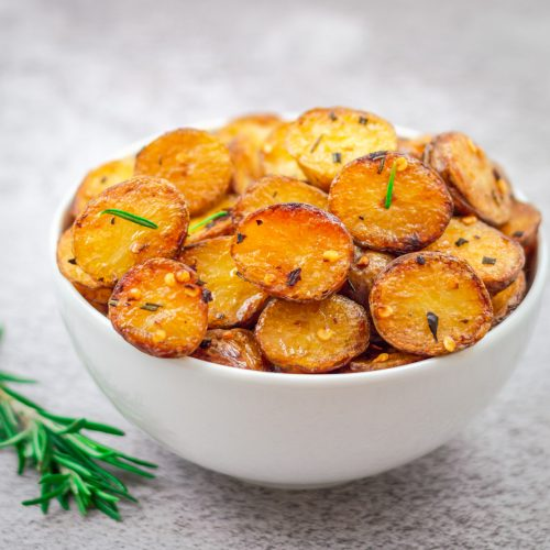 white bowl filled with roasted baby potatoes with sprigs of rosemary beside it placed on a grey backdrop.