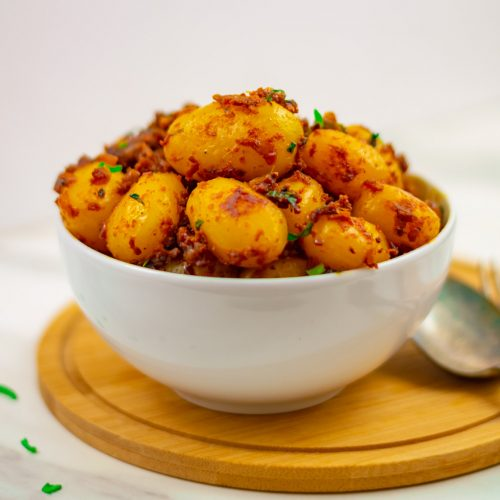 close up shot of bombay aloo placed in a white bowl on wooden board with spoon and fork on right side.