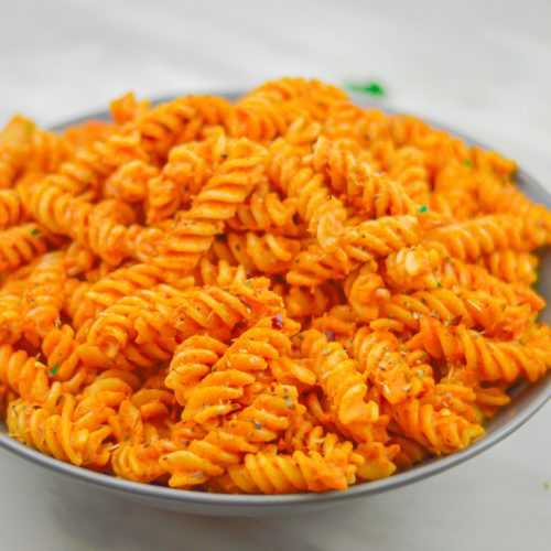 rotini pasta with vegetable sauce in a grey bowl placed on a marble with coriander leaf on side.