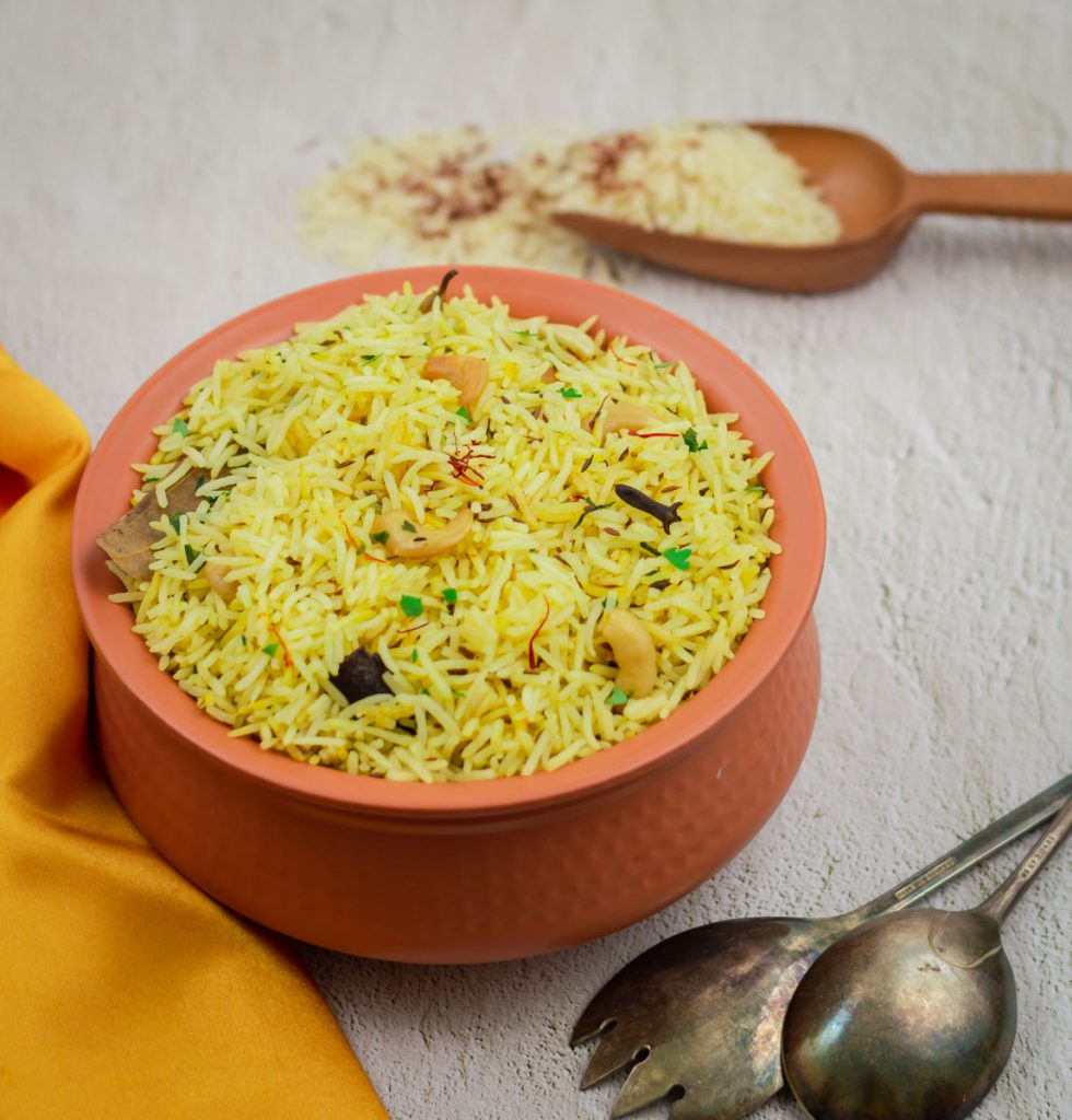 saffron rice in brown pot with orange cloth, spoon, fork and a wooden spatula with raw rice and saffron.