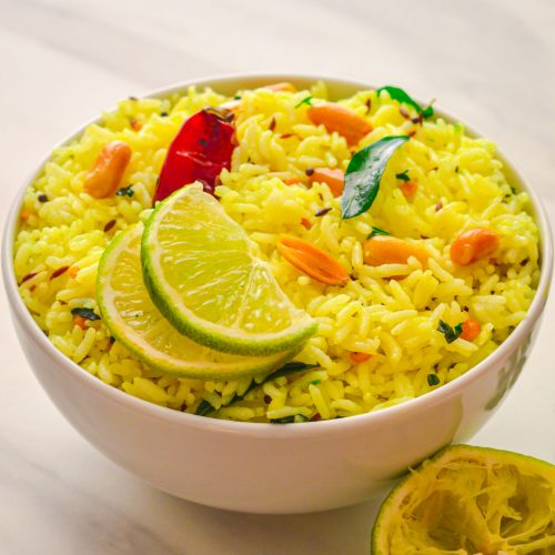 A white bowl of lemon rice topped with 2 half lemon slices, red chilli placed on a marble with a coriander leaves and squeezed lime on the side.
