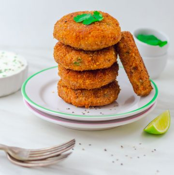stack of 4 sweet potato patties and 1 patty on side placed on 2 white side plates and yogurt dip bowl and coriander in 2 pinch bowls behind.