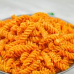 pin image of rotini pasta with vegetable sauce in a grey bowl on a marble with text overlay on top and bottom.