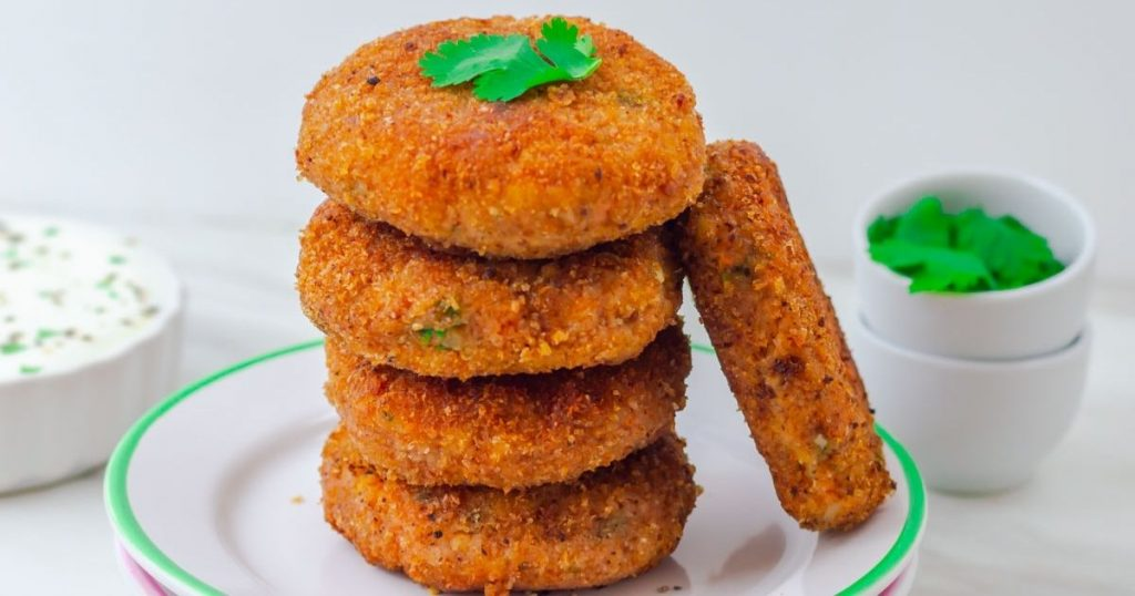 close up shot of stack of 4 sweet potato patties and 1 patty on side placed on 2 white side plates and yogurt dip bowl and coriander in 2 pinch bowls behind.