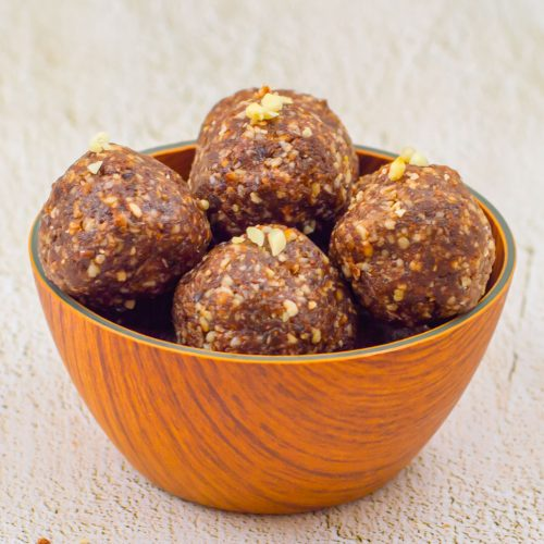 brown bowl of chocolate energy balls placed on a granite.