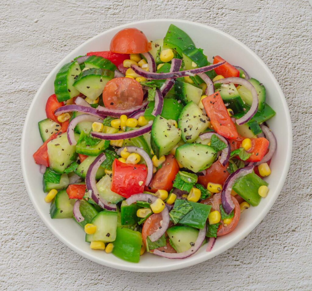 white bowl filled with corn, cucumber, tomato, onion, capsicum salad placed on a granite background.