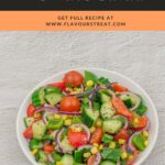 pin image with text overlay on top showing corn cucumber tomato salad in a white bowl placed on granite background.