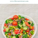 pin image with blue text overlay on top showing corn cucumber onion salad in a white bowl placed on granite background.