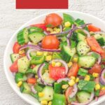 pin image with text overlay on top on red background showing onion cucumber tomato salad in a white bowl placed on granite background.