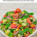 pin image with text overlay on top showing cucumber tomato mint salad in a white bowl placed on granite background.