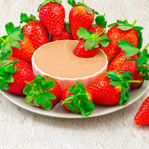 strawberry platter with a white bowl of chocolate dip in the middle placed on a granite background.
