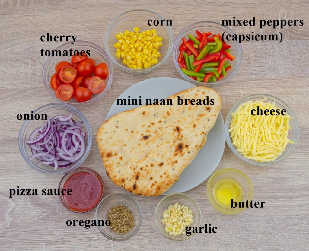 mini naan breads, vegetables, pizza sauce, cheese, oregano, garlic and butter kept in individual bowls placed on a wooden table.
